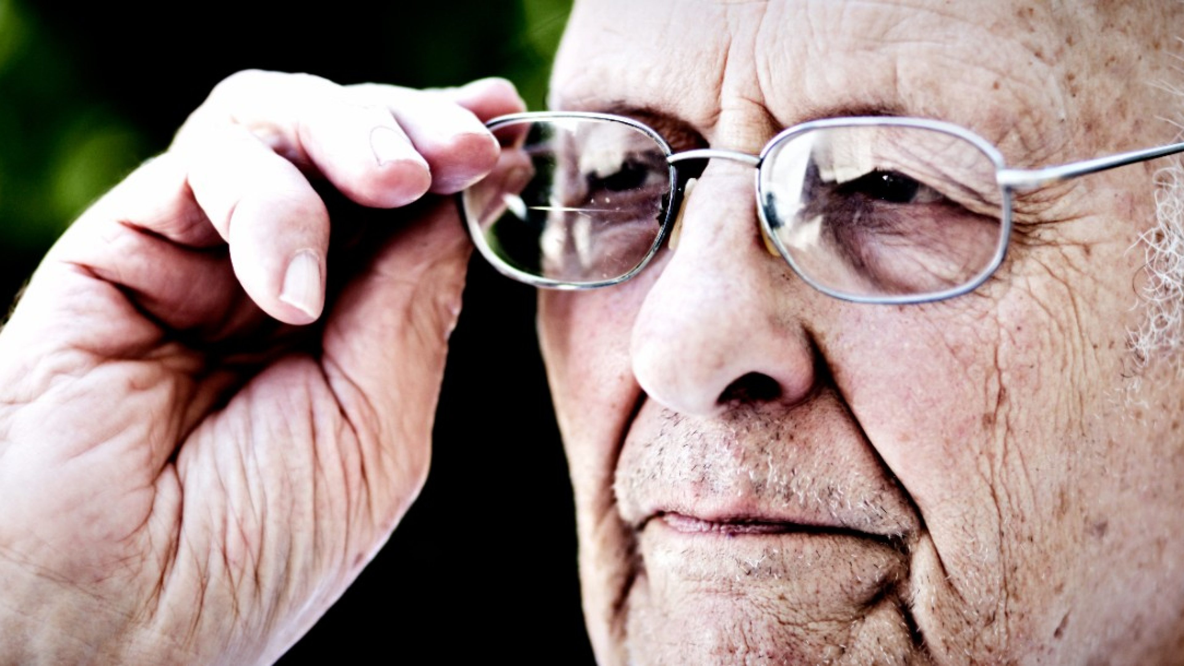 This 90 year old man adjusts his eyeglasses as he stands in his garden, looking serious.