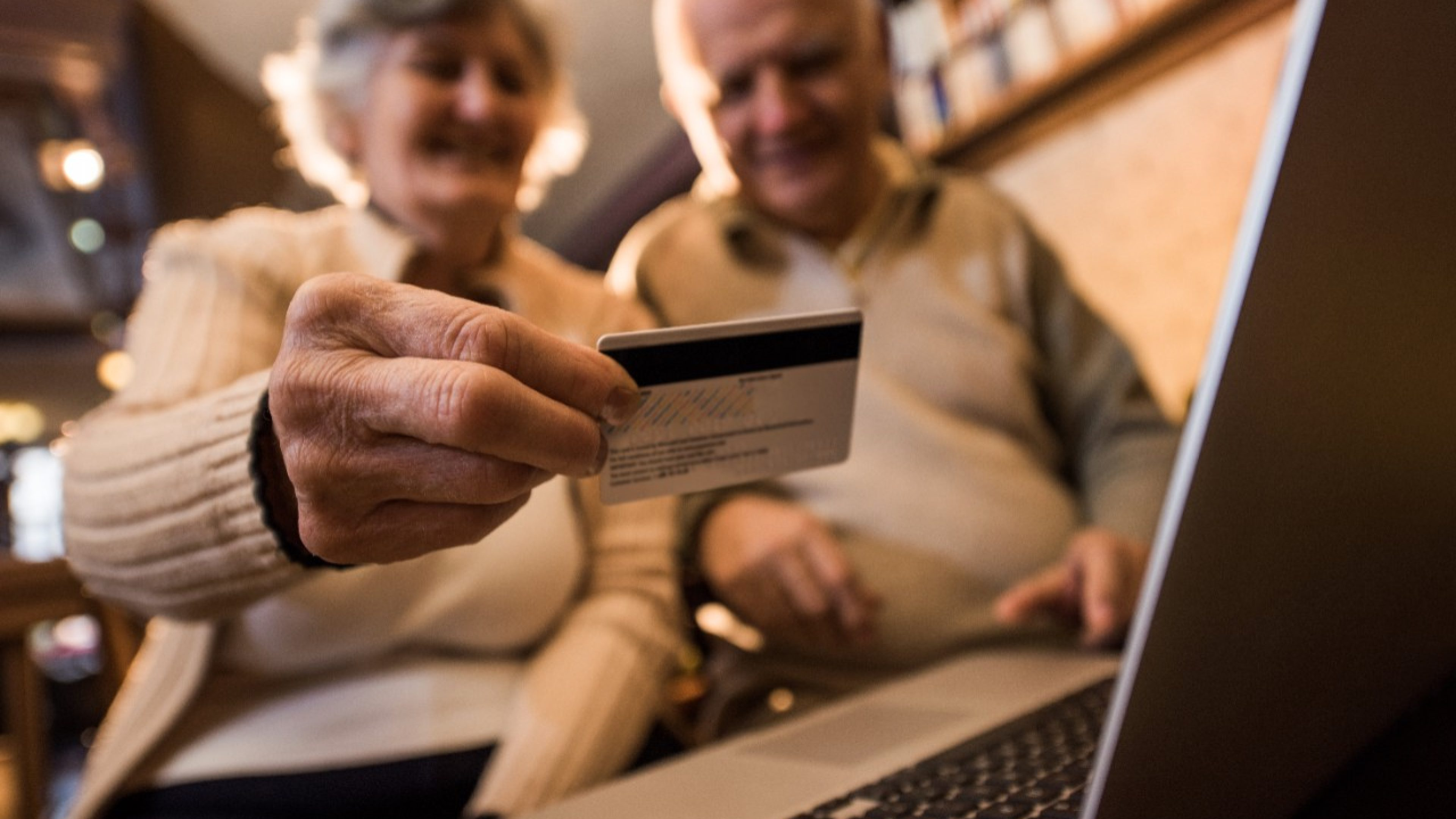 Close up of a senior man holding credit card and shopping with his wife via Internet.