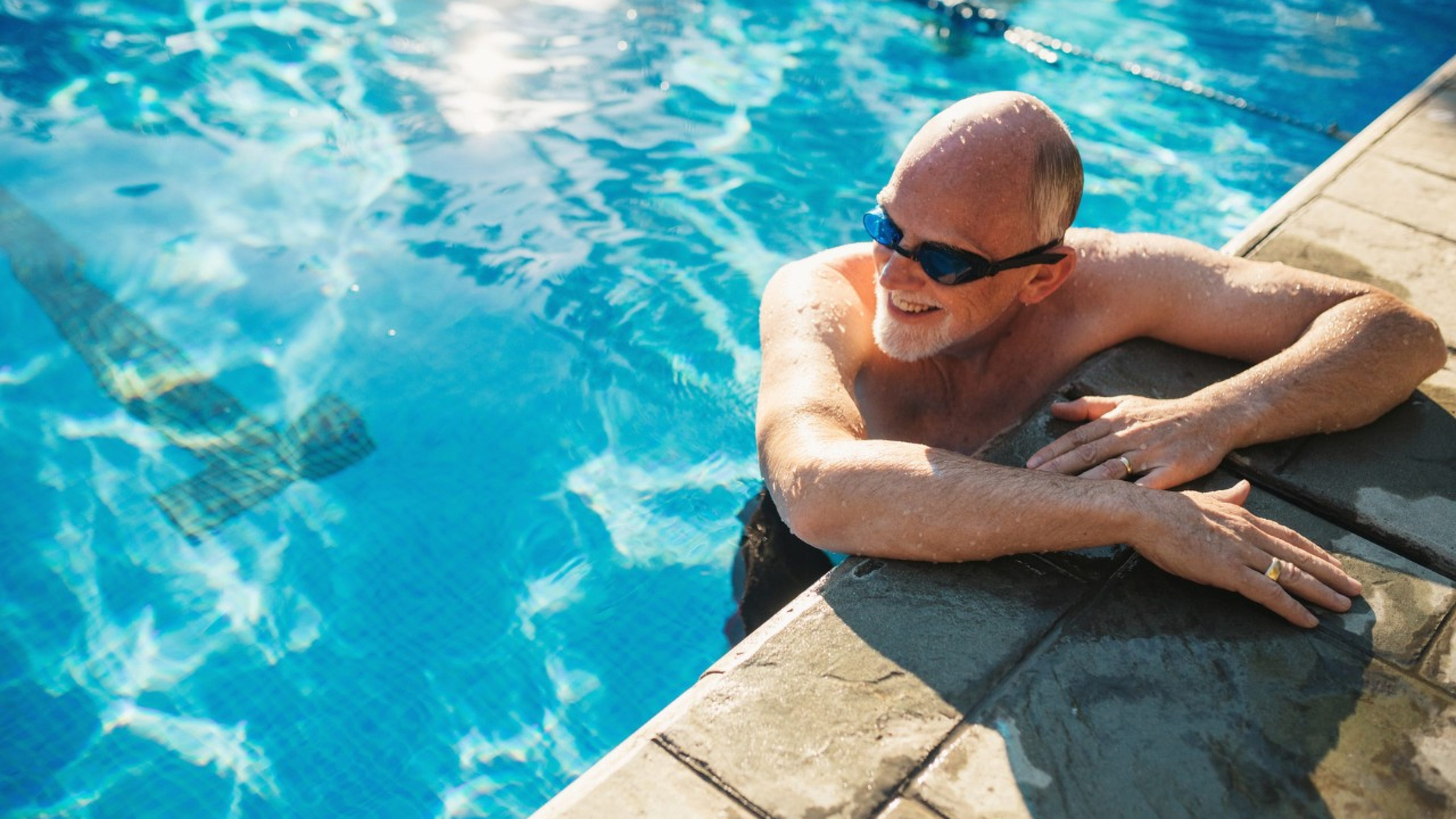 Active oler man working out at outdoor swimming pool
