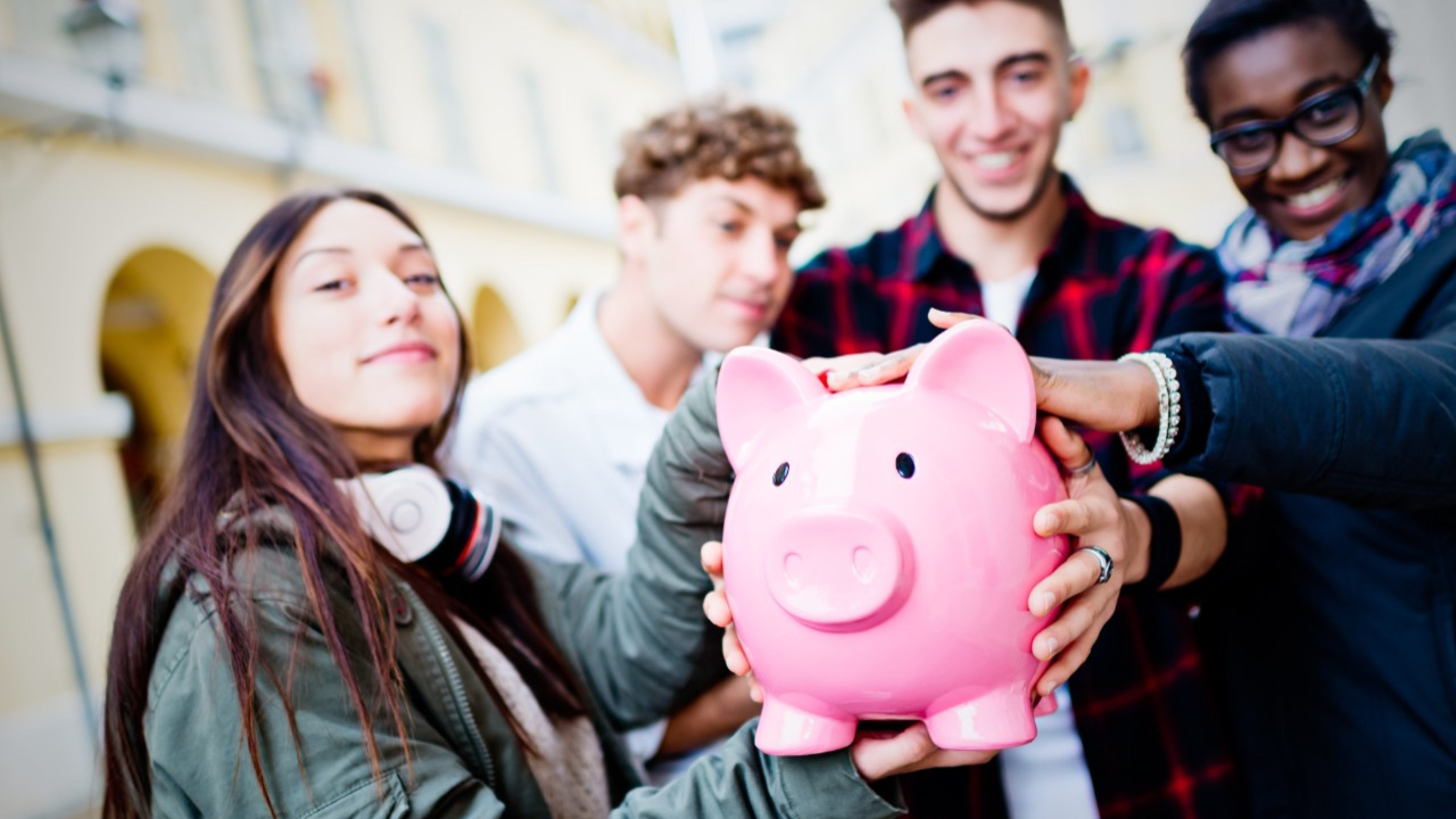 Group of mixed race people holding Piggy Bank